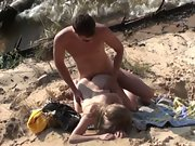 Naked couple has hump on the beach while swings lap at their feet
